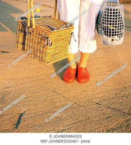 Woman with picnic basket, low section