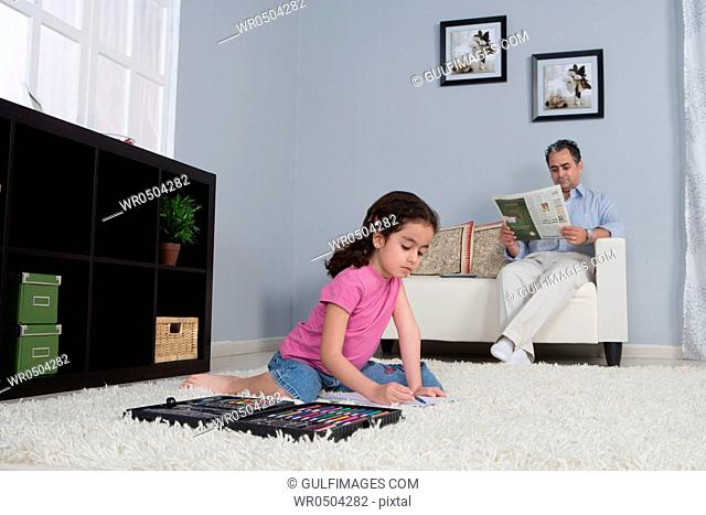 Father reading newspapers and daughter doing homework on the carpet