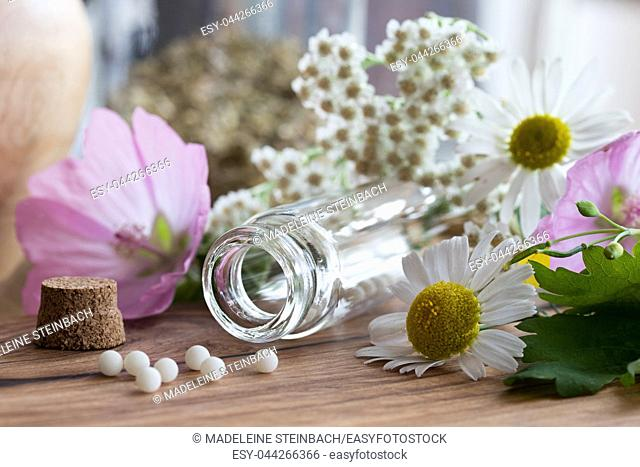 A bottle of homeopathic globules with chamomile, yarrow and other flowers in the background