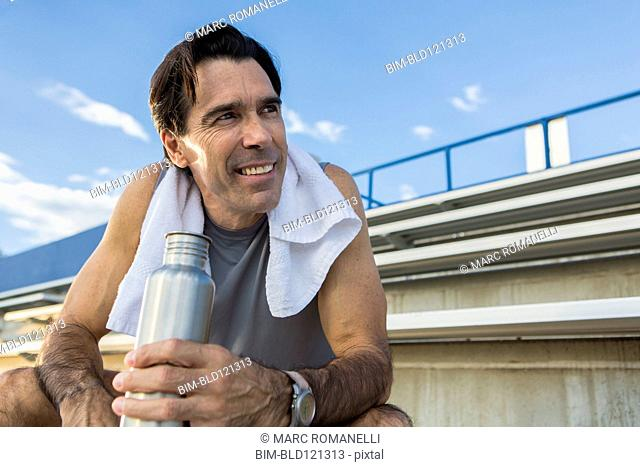 Hispanic man resting on bleachers