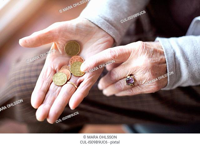 Senior woman counting coins in hand, close-up