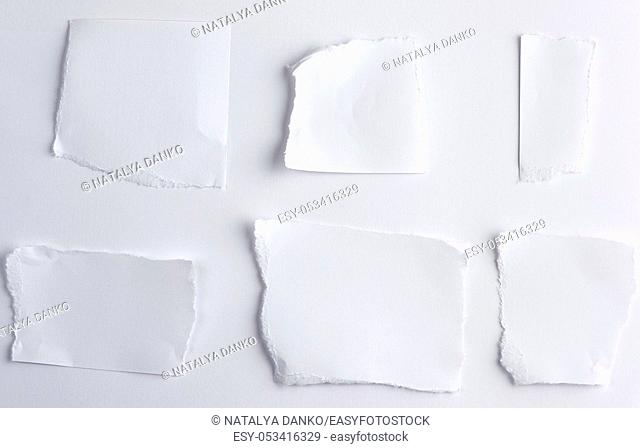 empty torn pieces of white paper on a white background, top view