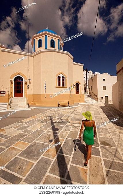 Woman walking near a colorful church in Hora, Serifos, Cyclades Islands, Greek Islands, Greece, Europe