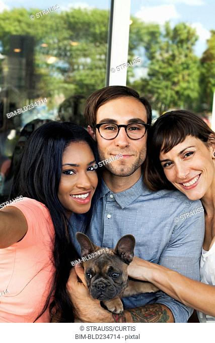 Friends posing with dog for selfie