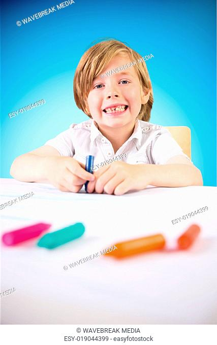 Composite image of cute boy colouring