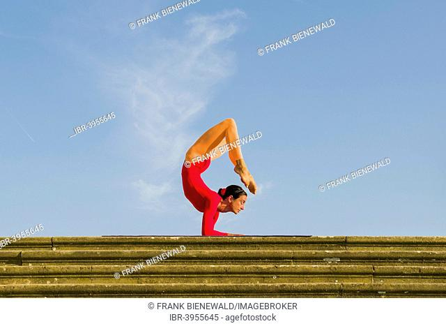 Young woman practising Hatha yoga, outdoors, showing the pose Vrischikasana, Scorpion pose