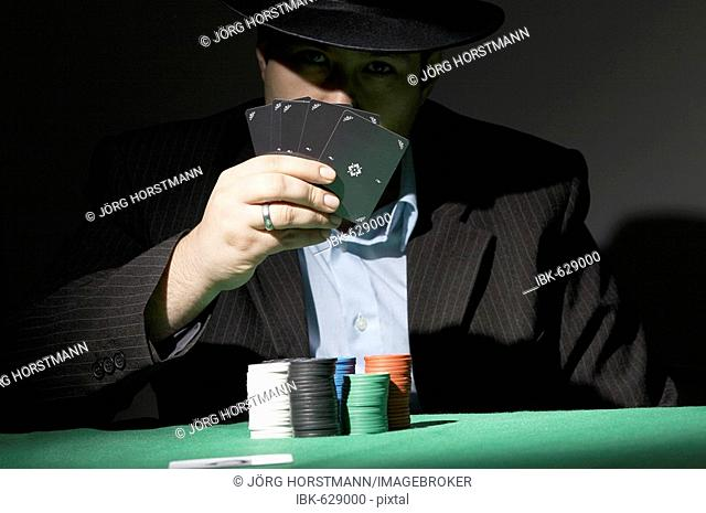 Poker player hiding his face behind cards