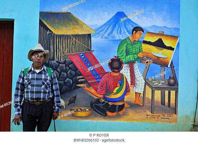man standing in front of a painting on a house wall showing a man painting a picture and a woman weaving a carpet, Guatemala, Atitlan lake, Santa Cruz la Laguna