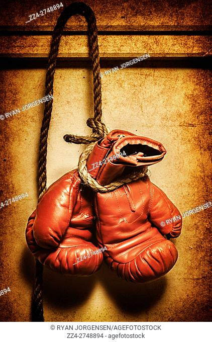 Vintage filtered close-up of boxing red gloves on rope hanging on wall. End Game