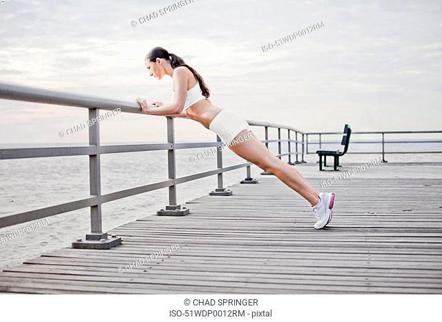 Woman doing push ups on wooden dock