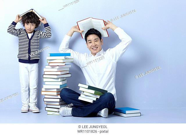 a father reading books with his son