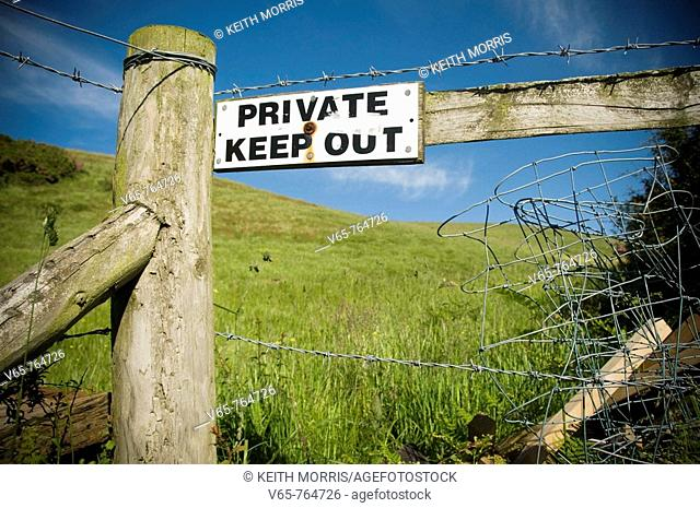 'Private Keep Out' sign on fence around a field