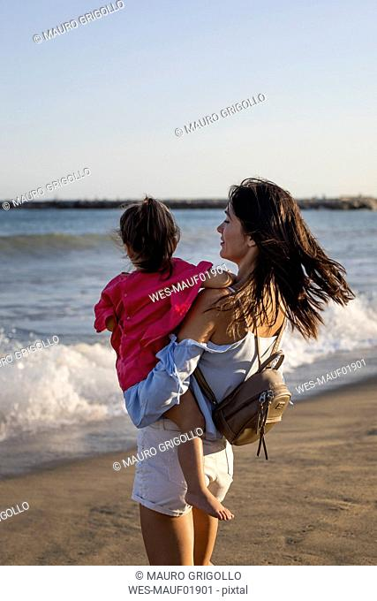 Mother and daughter standing on the beach at sunset