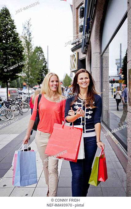 Two women with shopping bags in street