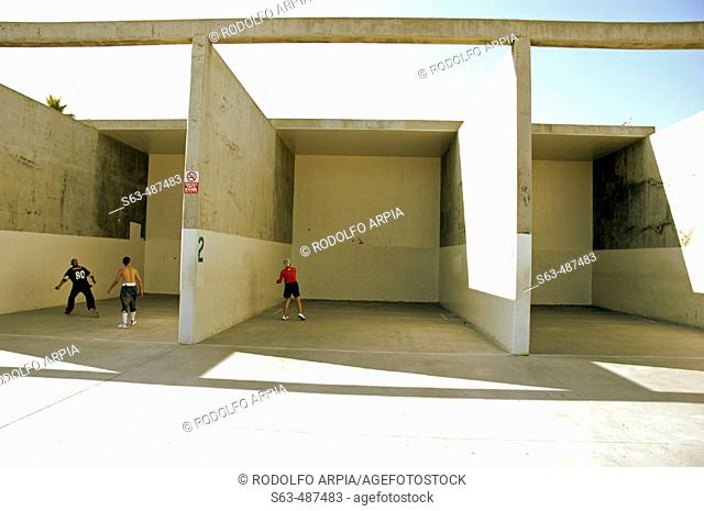Man playing ball by himself in one court and couple of friends playing in next court, Venice Beach, California United, States