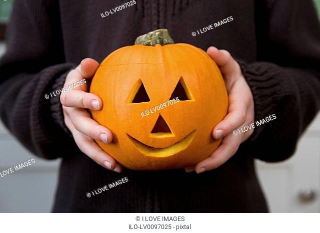 Close up of a boy holding a Jack'o Lantern for Halloween
