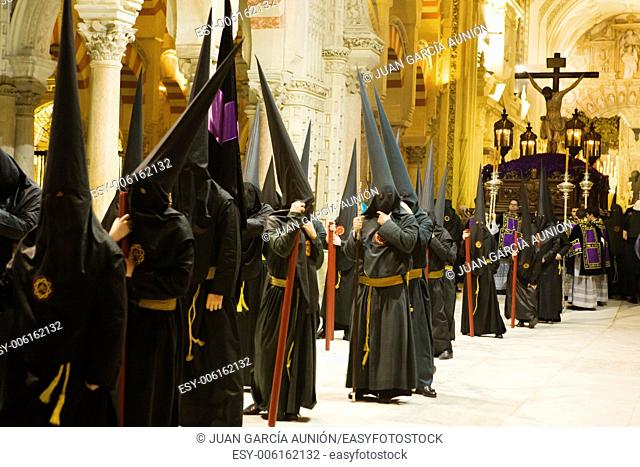 Easter nazarenes in black robe waiting inside the Mosque of Cordoba just before begin the procession. They carry candles and wearing the typical capirote that...
