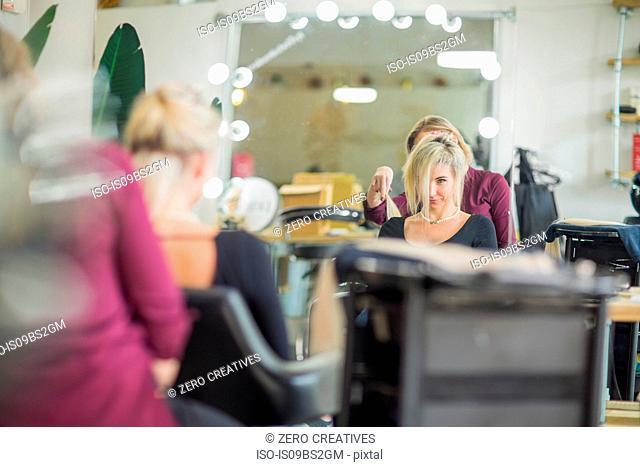 Hairdresser styling customer's hair in salon