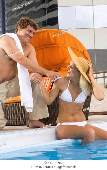 Playful young couple having fun poolside on rooftop terrace