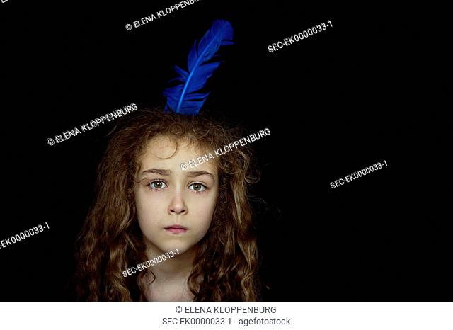 Serious looking girl (10-12) with feather in her hair