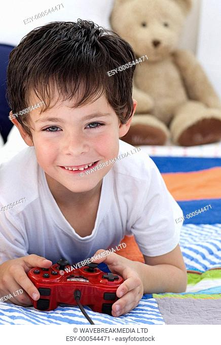 Little boy playing video games and lying on bed