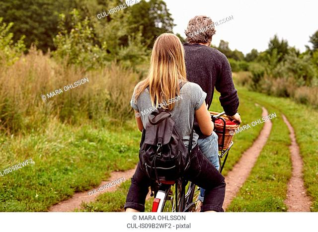Rear view of couple riding bicycle on rural dirt track