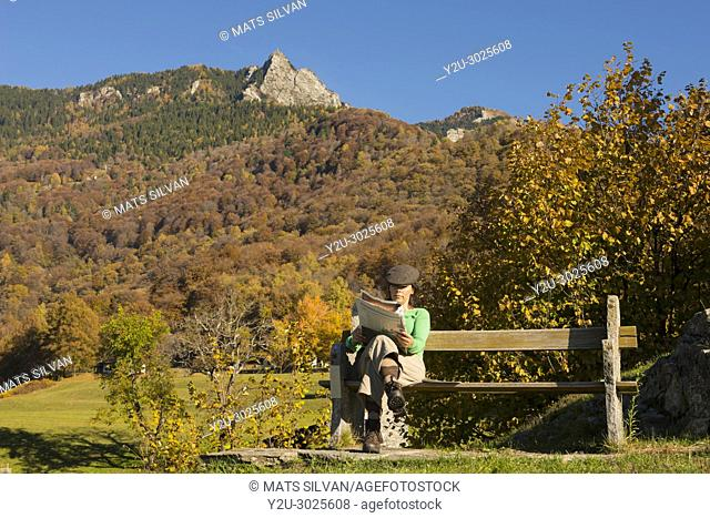 Woman Sitting on a Bench and Reading a Newspaper with Mountain in Background in Ticino, Switzerland