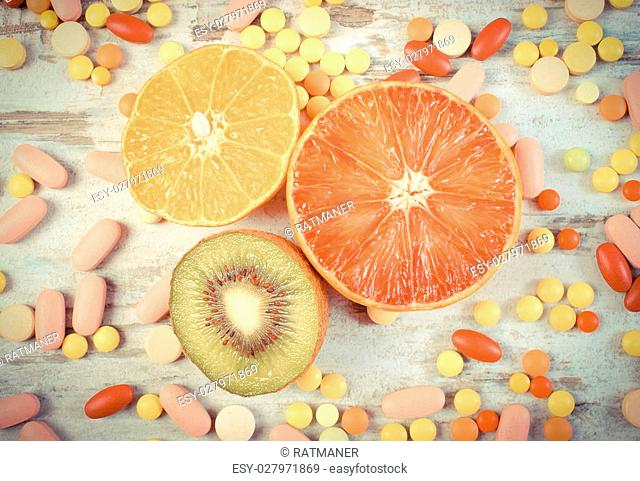 Vintage photo, Fresh natural fruits and medical pills, tablets and capsules on rustic wooden background, choice between healthy nutrition and medical...