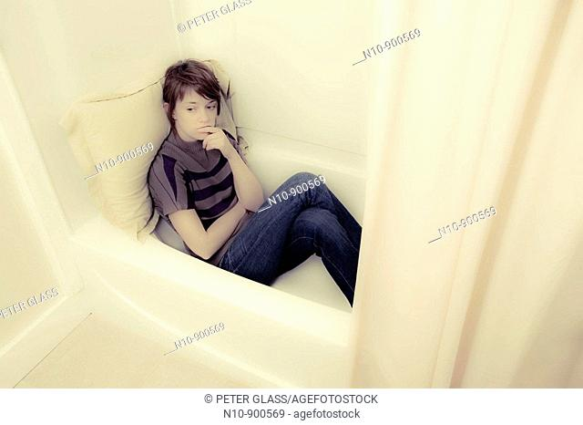 Young woman sitting in her bathtub