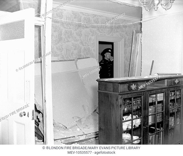 A salvage man, from the LSC, inspects a room following the removal/collapse of a plaster board partition