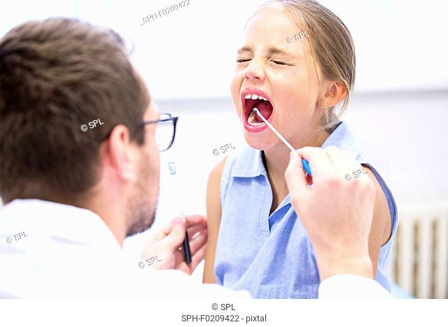 Doctor taking a swab from a girl's mouth