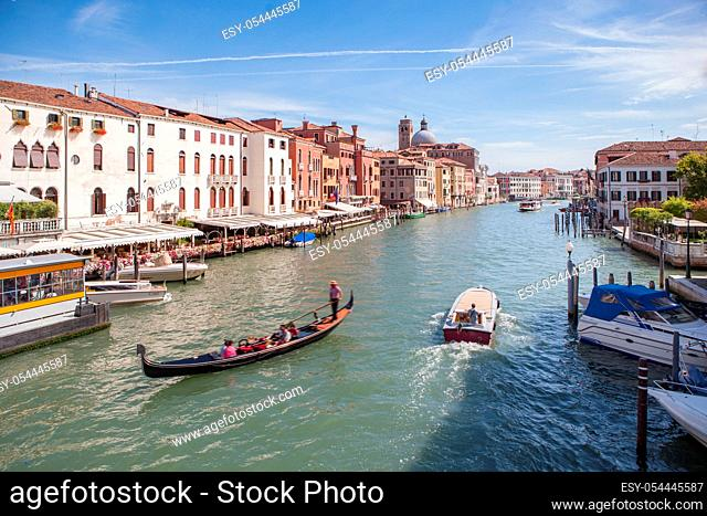 View of Grand Canal with gondolas and colorful facades of old medieval buildings from Rialto Bridge in Venice, Italy