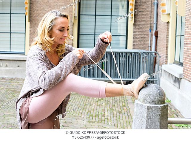 The Hague, Netherlands. 54 year old former ballet dancer tying up het pointers or ballet shoes or pointers after a small performance at Binnenhof