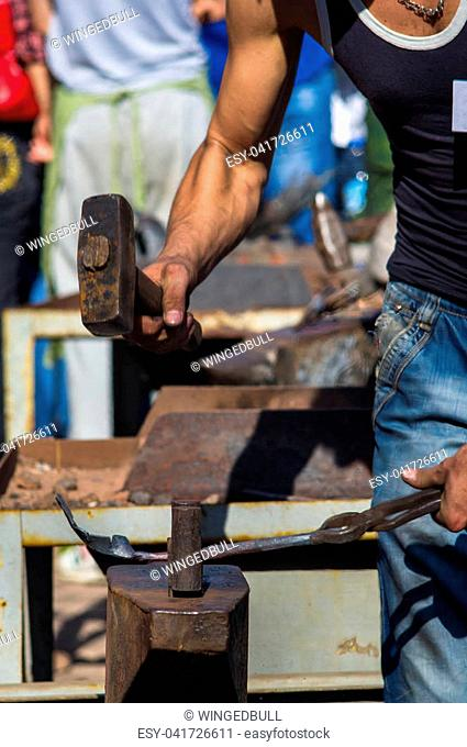 blacksmith performs the forging of hot glowing metal on the anvil, close-up