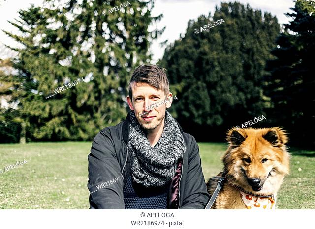 Portrait of smiling man sitting with Eurasier in park