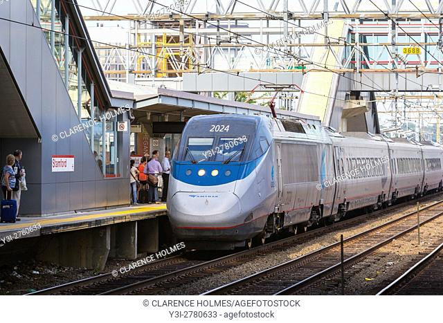 Passengers board a southbound Amtrak Acela Express train in Stamford, Connecticut