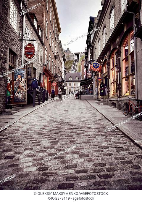La Chasse-Galerie boutique, Souvenirs du Lys and other shops and restaurants on a historic street Rue Sous-Le-Fort street with a funicular in the background in...