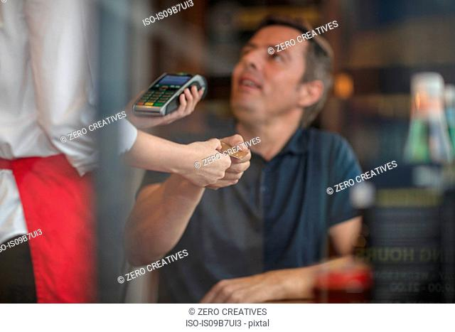 Customer handing credit card to waitress for payment on card machine