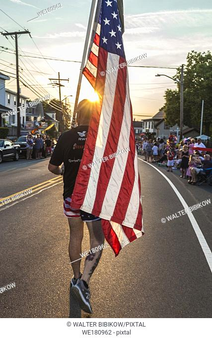 USA, New England, Massachusetts, Cape Ann, Gloucester, Gloucester Horribles Traditional Parade, July 3, man marching with US flag, NR