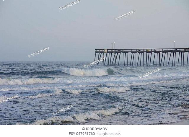 Waves crash on the pier on a stormy evening, Ocean City, Maryland, USA