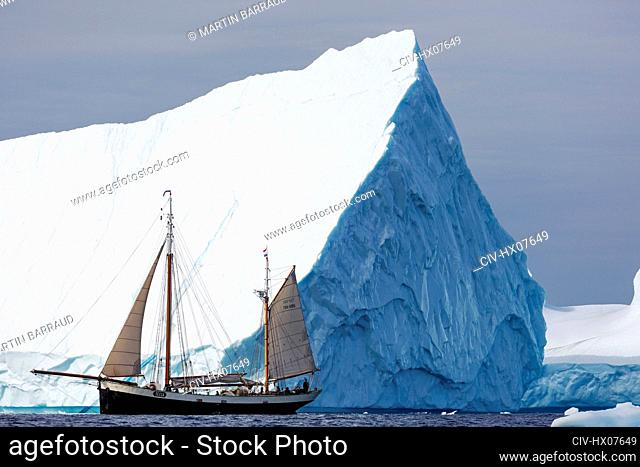 Ship sailing below majestic iceberg Atlantic Ocean Greenland