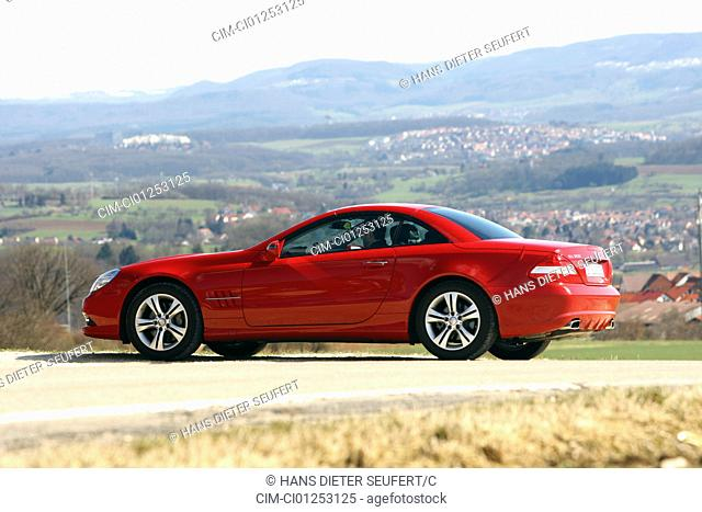 Mercedes SL 350, model year 2008-, red, standing, upholding, diagonal from the back, side view, country road, closed top