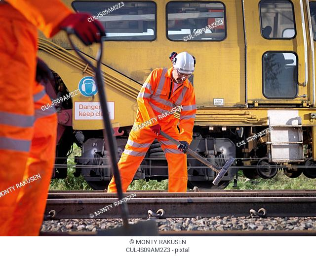 Railway maintenance worker tightening bolts on track