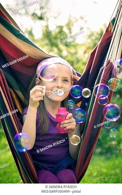Portrait of smiling little girl blowing soap bubbles