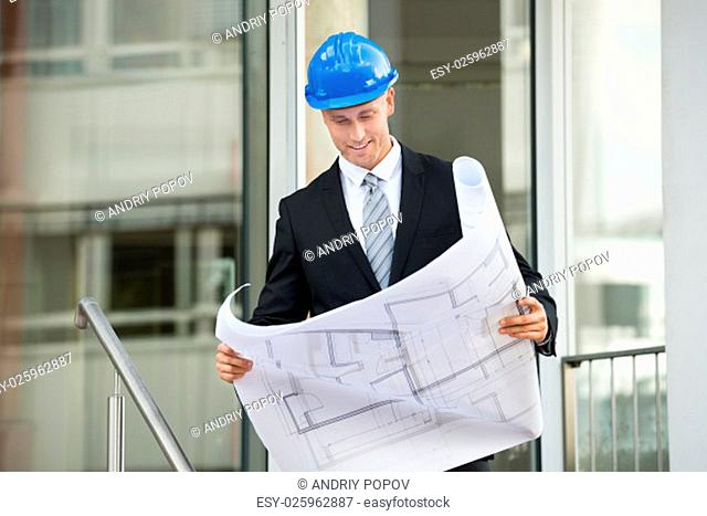 Young Engineer With Hard Hat Holding Blueprint In His Hands