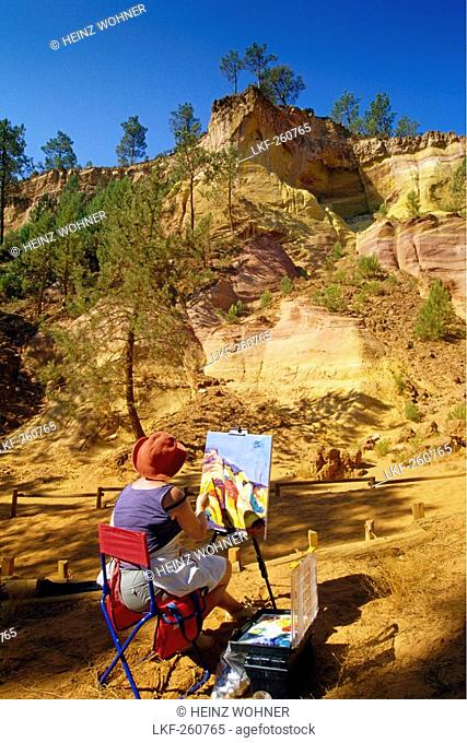 Paintress with easel at the ochre rocks at Val de FÚes under blue sky, Vaucluse, Provence, France, Europe