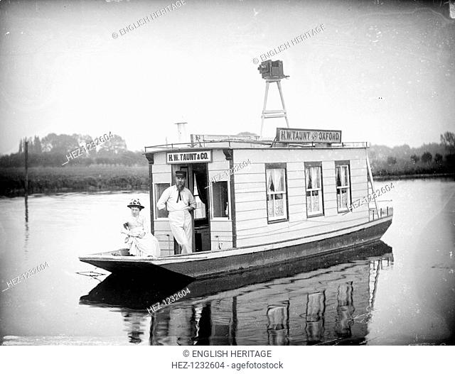Henry Taunt on his floating studio near Oxford, Oxfordshire, 1895. Henry Taunt is pictured on the houseboat which he used for river photography with a lady
