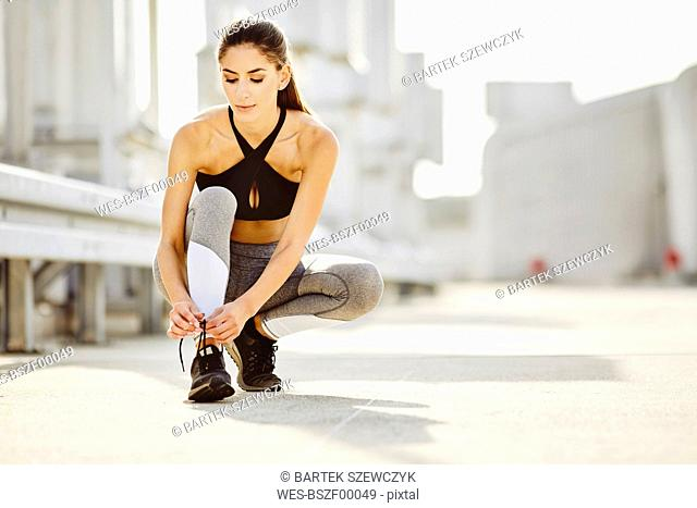 Young woman tying her shoes before workout