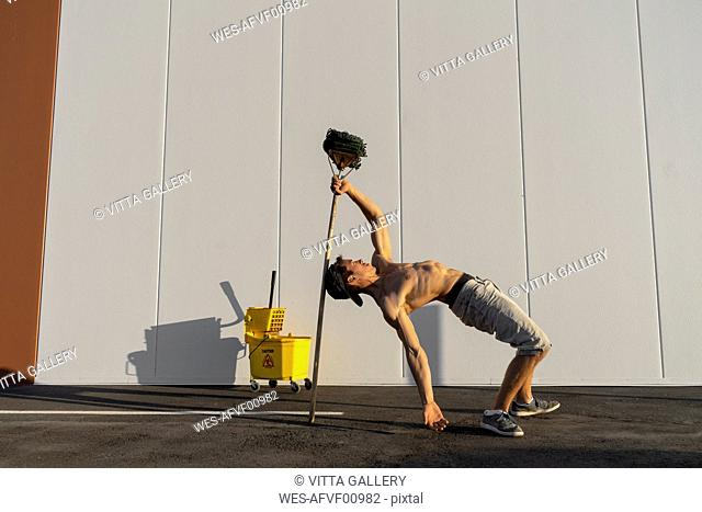 Acrobat playing with cleaning bucket and mop