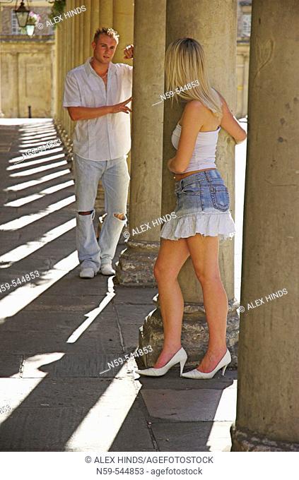 Young couple flirting amdist classic collonade